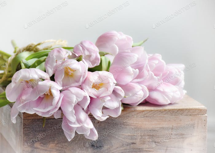 Blush pink tulips on a rustic wooden stool