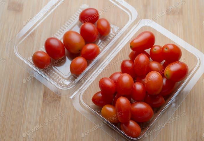 Los tomates rojos en el recipiente de plástico