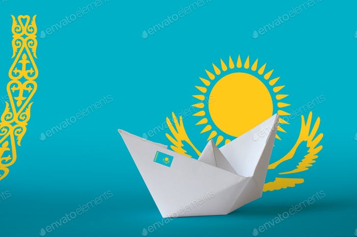 Kazakhstan flag depicted on paper origami ship closeup. Oriental handmade arts concept