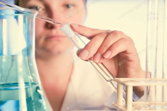 Chemistry and science. Woman holding a flask with fluid. Chemical scientist. Chemical industry