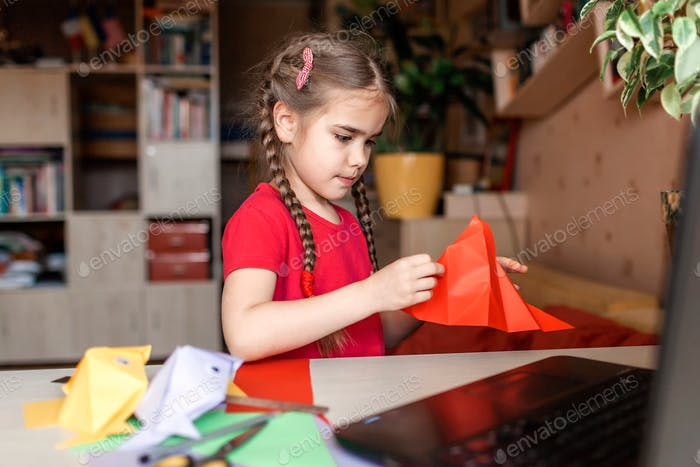 Girl doing origami fish with color paper looking video on laptop
