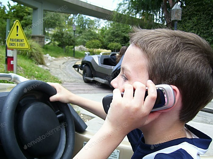 Learned from parents, boy holds a cell phone to ear while driving cars at Disneyland Autopia.