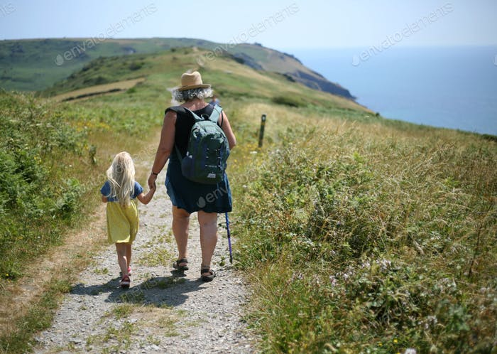Grandmother and granddaughter holding hands walking on a costal path