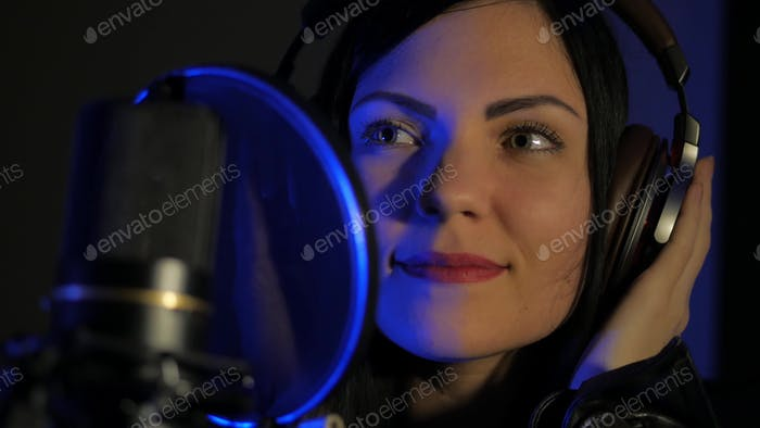 Woman with headphones in recording studio