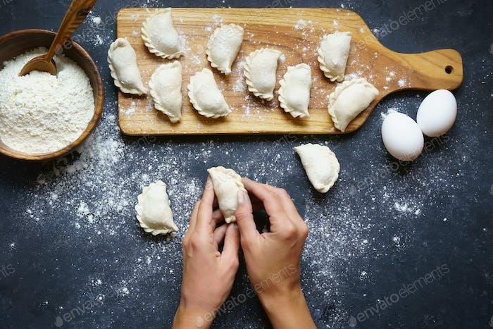 human hands preparing cherry dumplings pierogi