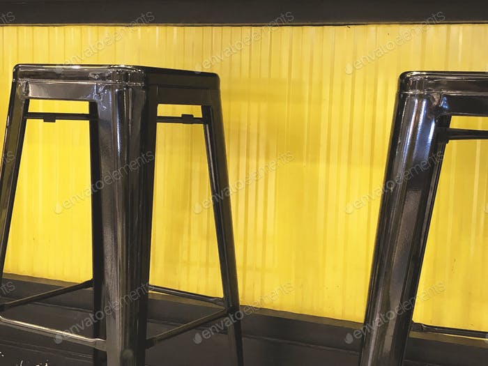 Black stools at yellow bar