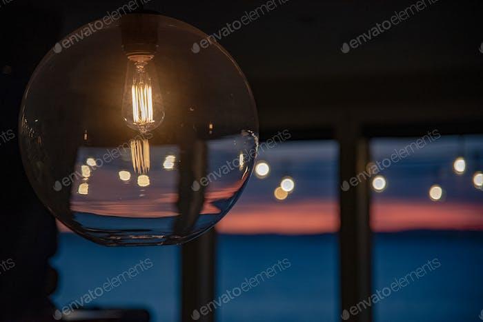 Lightbulb lit in modern housing