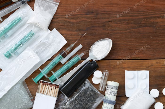 A lot of narcotic substances and devices for the preparation of drugs lie on an old wooden table