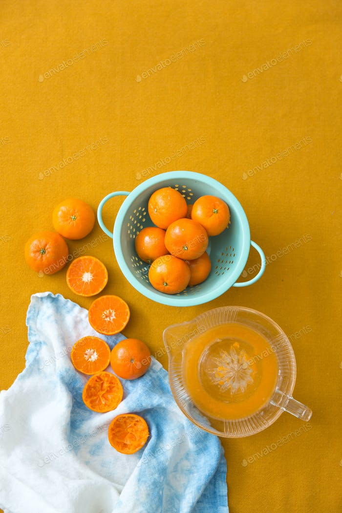 Clementines and a juicer on a yellow background