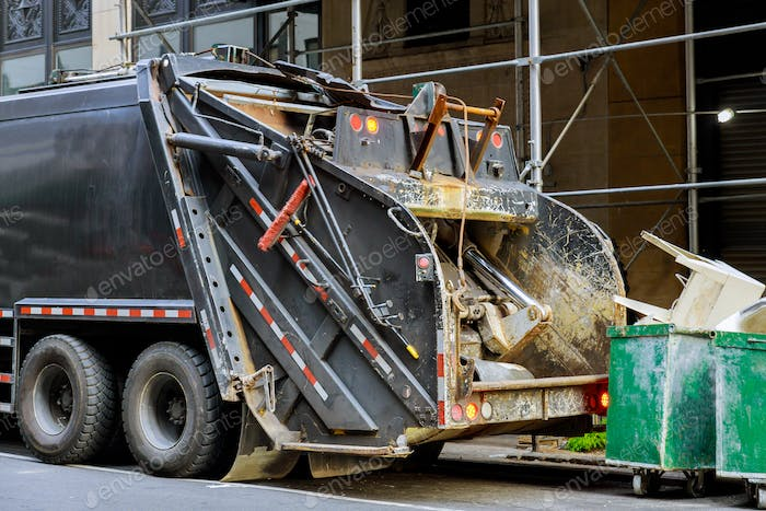 City building demolition cleanup with dumpsters filled to the urban municipal garbage collector tru