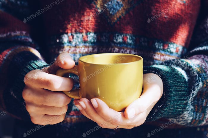 The girl is warmed by hot tea during an autumn season