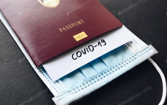 Close-up photo of a passport with a covid-19 report and face mask.