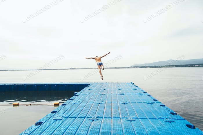 man diving into the water from a plastic floating pier