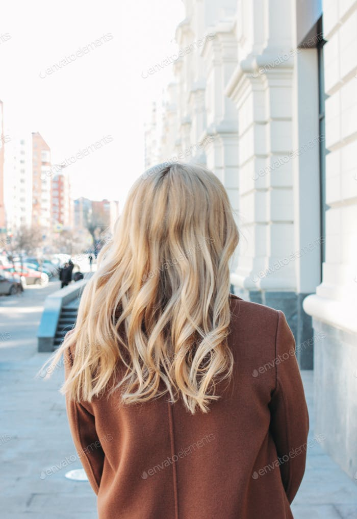 Stylish fashionable woman wearing coat with curly blonde hair at the street