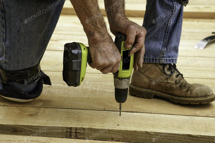 A construction worker's hands using a power drill to secure wood boards to a patio deck.