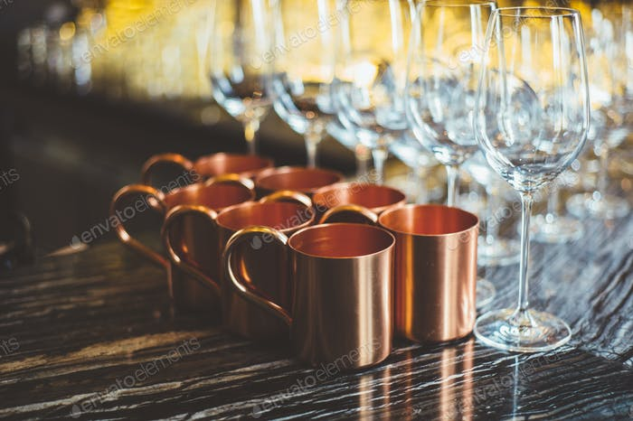 Brass cups and glasses on table