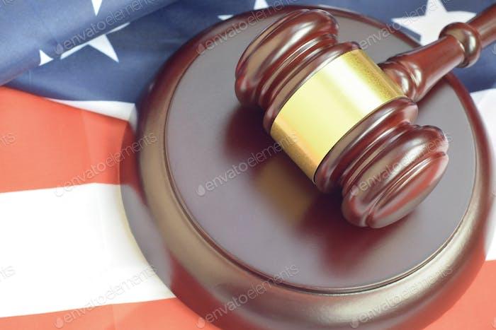 Mazo de justicia en la bandera de los Estados Unidos en una sala de audiencias durante un juicio judicial