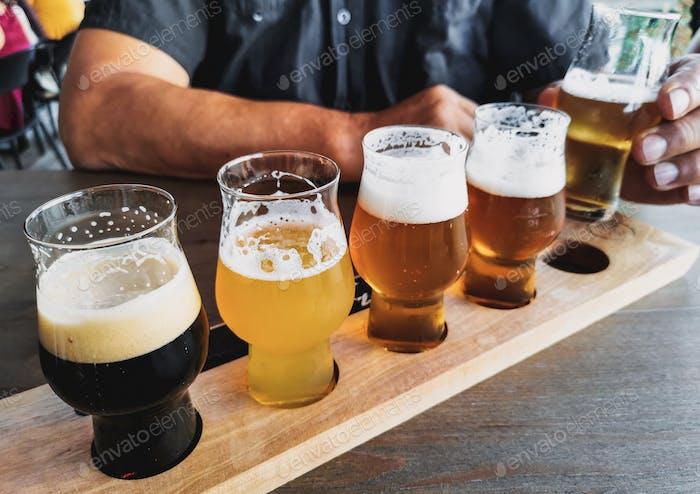 Mann schmeckt Bier. Verkostungsbrett mit Biergläsern