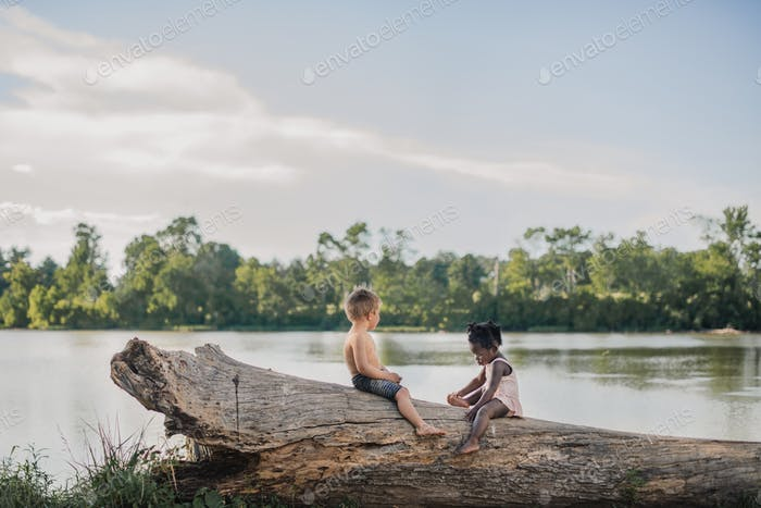 Boy and girl, brother and sister, sitting on a log by a lake in swimsuits in summertime