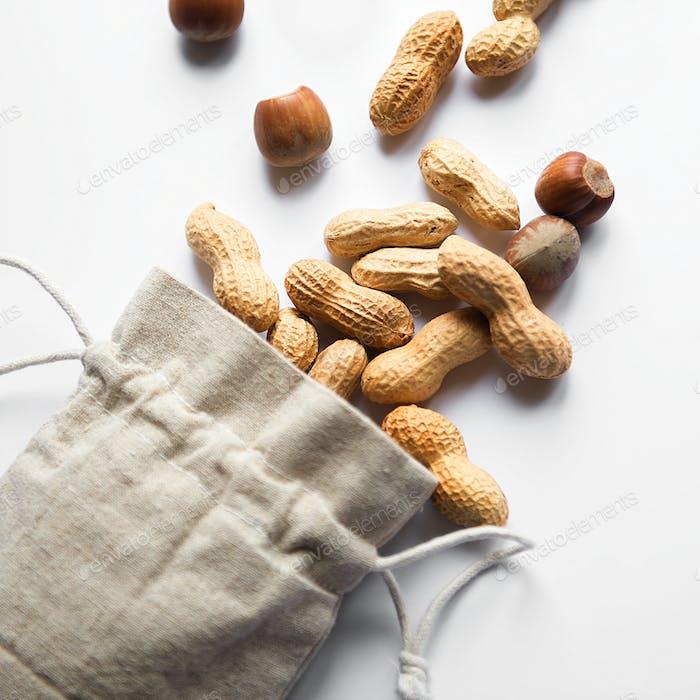 Umweltfreundliche Stofftasche mit Erdnüssen und Haselnüssen auf weißem Hintergrund
