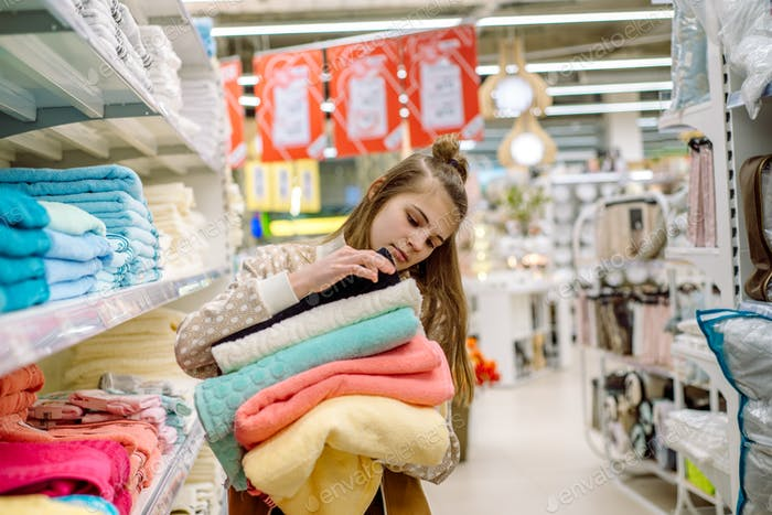 Teen girl choose towels in the store