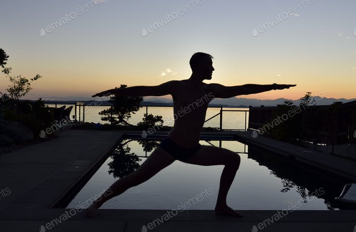 Man in silhouette next to swimming pool at sunset doing a Warrior yoga pose. RLTheis