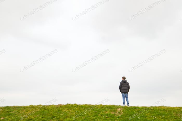 Person standing on the horizon above a grass field against a grey sky depicting loneliness, thinking