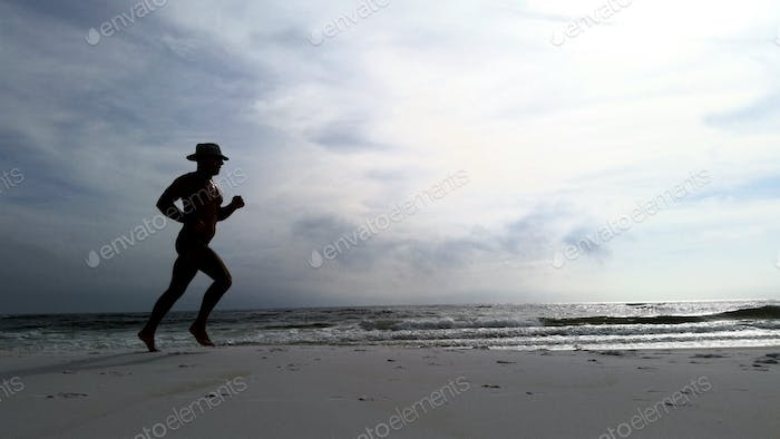 Silhouetted older fit man runs for fitness on the shore of Florida getting fresh air.