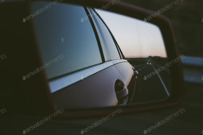 Focus on foreground of a rear mirror. Driving. Road trip. Vanishing point.