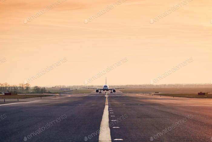 Front view of airplane on taxiway after landing. Traffic at airpot at sunset.