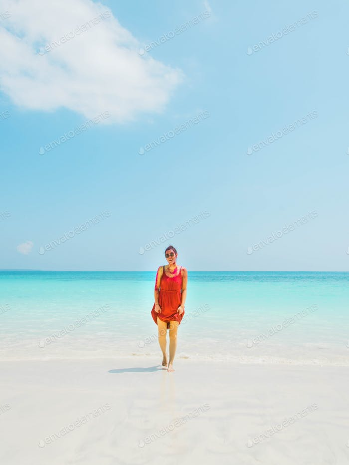 Portrait of a woman with a red dress walking on a beach in the Andaman Island - India