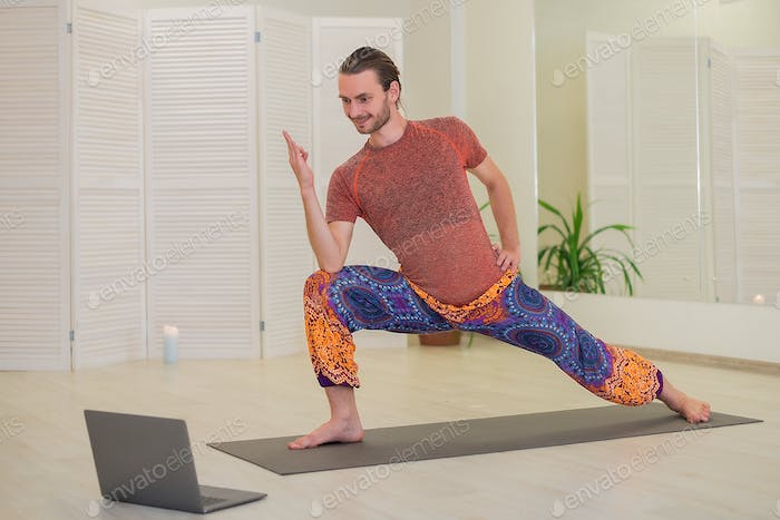 A young male yogi practices and teaches yoga online on a laptop in the Studio.
