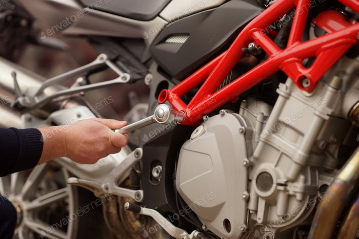 Technician hands of motorbike mechanic repairing the vehicle at the service with a wrench