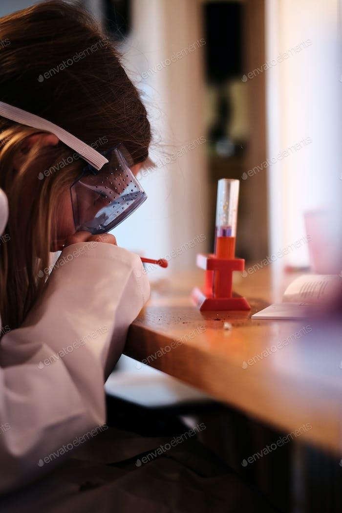 Ein Mädchen, das in Brille und ein weißer Labormantel gekleidet ist, führt ein Experiment mit Chemikalien in einem Test durch.