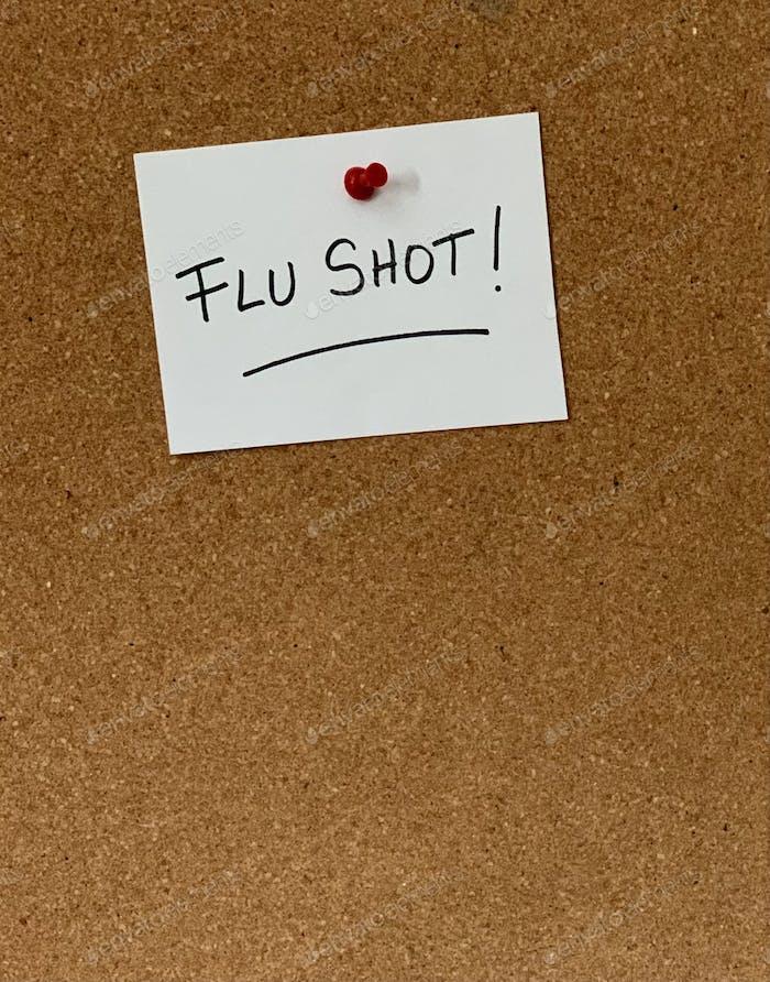 Erinnerung an das Grippe-Schusszeichen auf einem Korkbrett. Es ist Grippesaison, Zeit für deine Grippe-Impfung! Wilde Worte