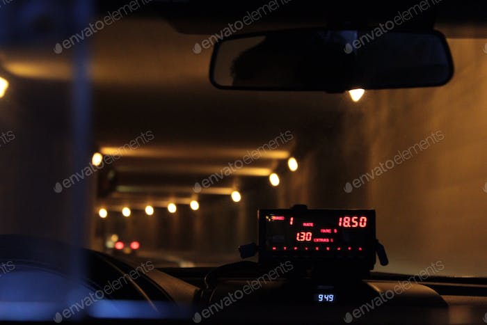 The meter is running in a cab going through a tunnel.