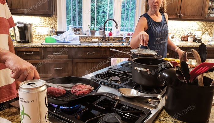 Married couple cooking together while both confined at home due to coronavirus concerns and wife