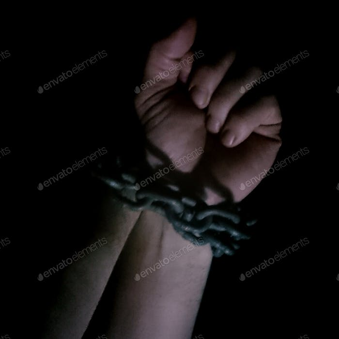 Male hands handcuffed with chains, shadow and mystique, drama, dramatic, abuse, violence, mistreated