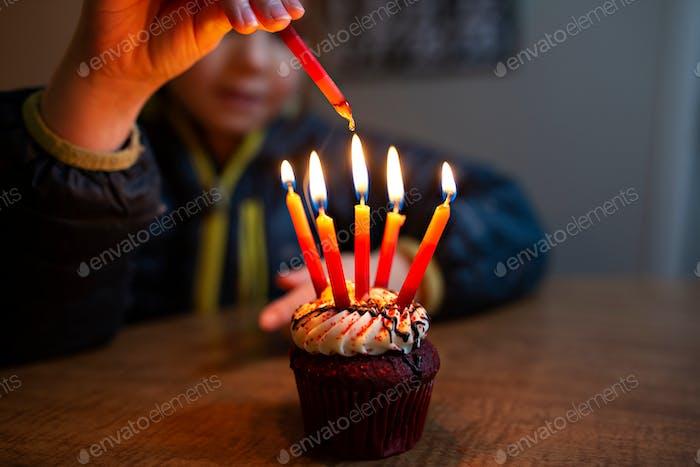 little girl lighting birthday candles on a birthday cupcake