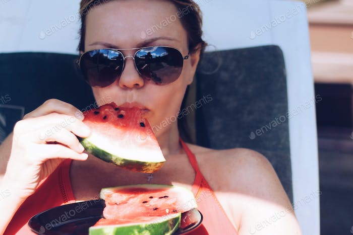 The girl sunbathes and eats watermelon