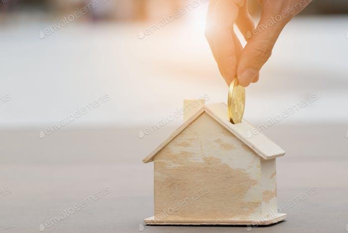 Nahaufnahme einer Hand, die eine goldene Münze in ein Haus Mock up legt