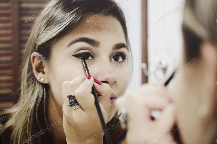 Woman in front of a mirror putting makeup on