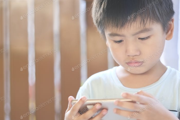 Close-up portrait of a young kid using tech device with lens flare
