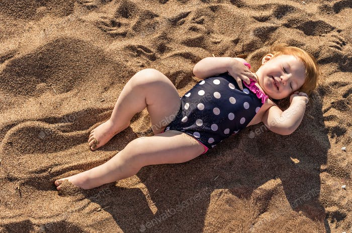 A little girl in a bathing suit is lying on the sand.