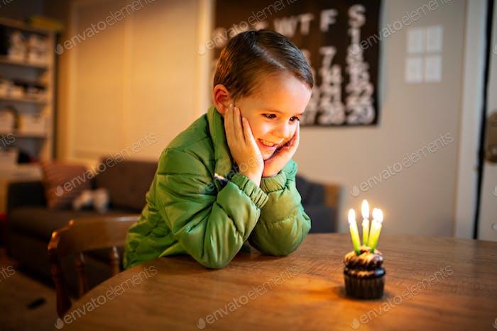 kleiner Junge blickt mit Aufregung auf einen Geburtstagskuchen