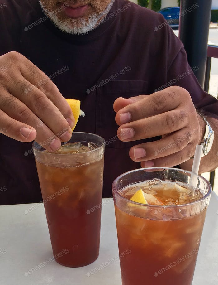 Man adding lemon to his ice tea
