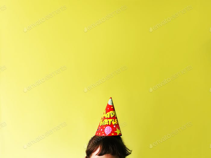 Happy birthday cap on head on bright festive background/ surprise greetings celebration holiday p