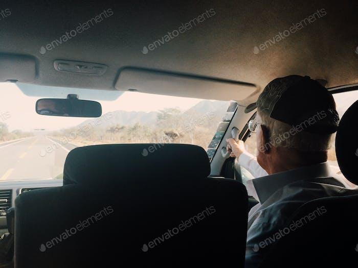 Senior citizen riding in a shuttle in the desert