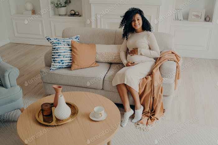 Young african pregnant woman in casual dress caressing her belly while sitting on couch at home