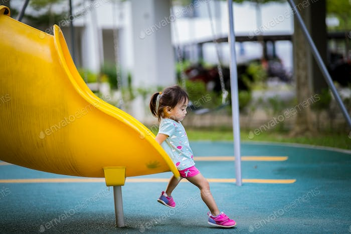 Toddler at the end of the slide in the playground.